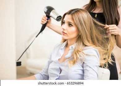 Pretty young Caucasian woman getting her hair dry with a blowdryer at a hair salon
