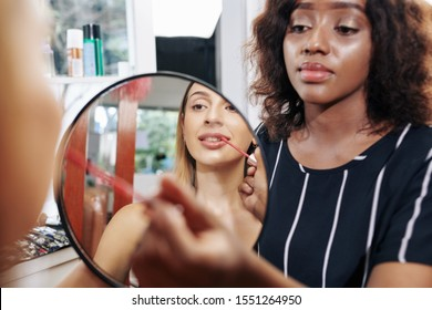 Pretty young Caucasian woman looking at small circle mirror when make-up artist applying peach gloss on her lips