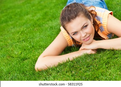 pretty young caucasian woman lying on grass looking at camera