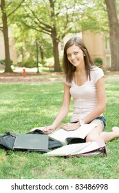 pretty young college or high school student with laptop and books