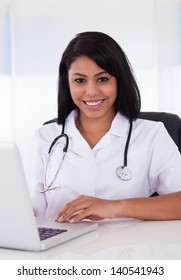 Pretty Young Confident Doctor Using Laptop In Clinic