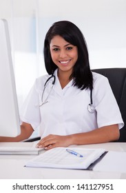 Pretty Young Confident Doctor Using Computer In Clinic