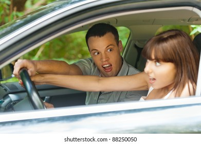 pretty young couple man woman sitting car surprised hold hands steering wheel background summer green park