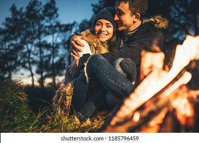 Pretty young couple relaxing near bonfire in the forest at evening time