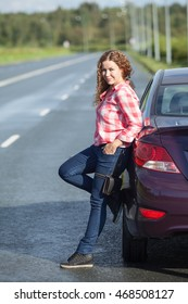 Pretty young curly hair Caucasian woman standing near car on the asphalt road