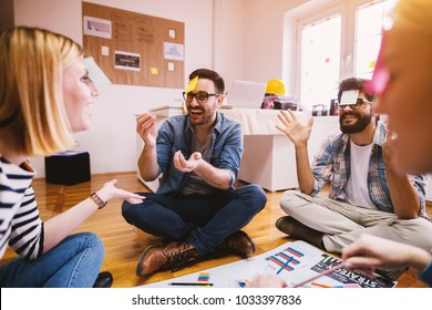 Pretty young designer coworkers enjoying free time and raising togetherness and team spirit while sitting in a circle on the floor of the office and playing games with paper stickers on the forehead.