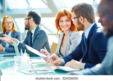 Pretty young employee looking at her colleague during discussion of data