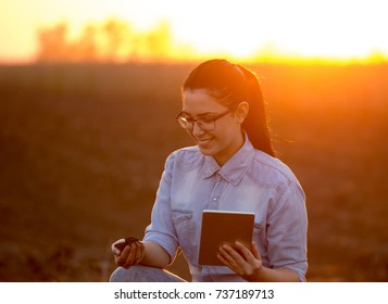 Pretty young engineer woman holding dirt in hand and tablet. Researching soil in field