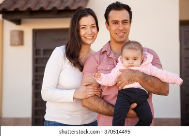 Pretty young family with a baby standing in front of their brand new house and smiling