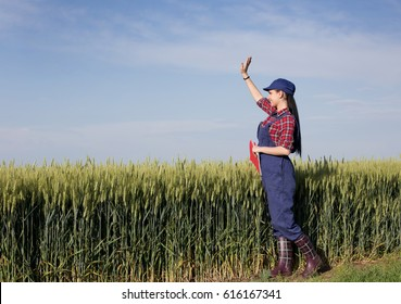Pretty young farmer woman standing in front of green wheat field and waving hand