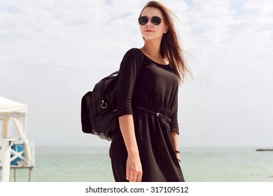 Pretty young fashion beautiful sensual brunette woman posing outdoor in summer in black dress with backpack on the beach near the sea
