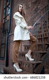 pretty young fashion woman walking upstairs on the street wearing white coat and beige trousers