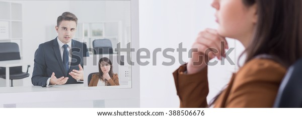 Pretty young female boss talking with applicants online on video conference