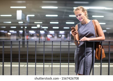 Pretty, young female commuter waiting for her daily train in a modern trainstation, using her cellphone while waiting (color toned image)