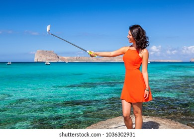 Pretty young female dressed in a coral clothes having fun making selfie with a selfiestick on the background of the azure sea