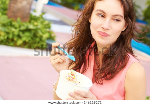 Pretty young female eating ice cream while looking away. Horizontal Shot.