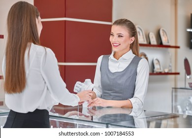 Pretty young female jewelry worker in white blouse and grey uniform is helping to choose a necklace for a female visitor wearing smart clothes such as black skirt and white blouse in a jewelry store.