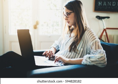 Pretty young female manager working via laptop at vintage loft, hipster girl using modern notebook at coffee shop, attractive businesswoman using portable computer during a break, flare light