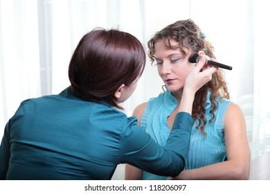 Pretty young female model having her makeup applied before her photoshoot.