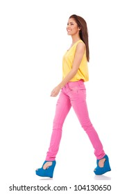 Pretty young female model in pink jeans walking on white background and smiling - Copyspace