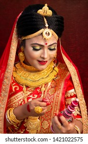 A pretty young female model wearing traditional Indian / Bangladeshi bridal outfit with heavy gold jewelry and makeup