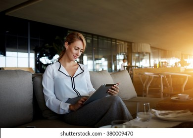 Pretty young female search information on digital tablet while waiting for her friend in modern cafe interior,elegant businesswoman using touch pad while reading feminine website of fashion and health