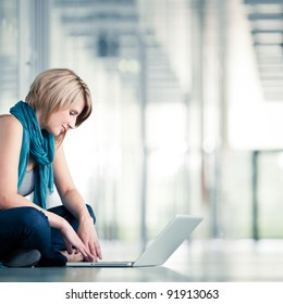 Pretty young female student with a laptop computer on college/university campus (shallow DOF; color toned image)