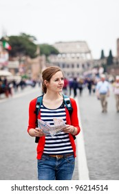 Pretty young female tourist holding a map while walking along the Via del Fori Imperiali avenue in Rome, Italy (with Colosseum in the background)