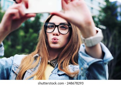 Pretty young female tourist makes selfie. Beautiful urban woman taking picture of herself. Filtered image.