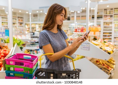 A pretty young female, using her mobile phone in modern market