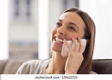 Pretty young female using white mobile phone at home smiling