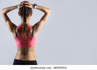 Pretty young fitness person with perfect body wearing red sportswear bra standing against grey background. Sporty model girl wearing smartwatch posing with hands behind head. Back view. Copy space