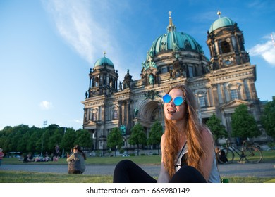 Pretty young gil sitting in front of Berlin Cathedral at beautiful sunset and eat chocolate