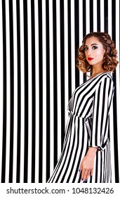 Pretty young girl at the background of black and white vertical stripes
