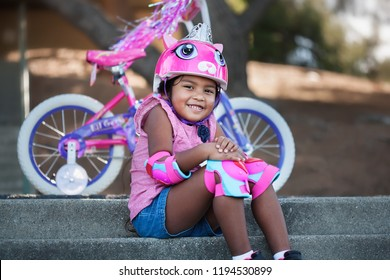 Pretty young girl with bicycle safety gear smiling and sitting in front of her new bicycle with training wheels in an outdoor park