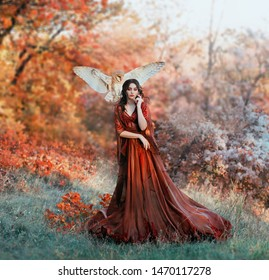 pretty young girl with black hair in cold forest, orange foliage of trees, fairy of autumn season in long red burgundy vintage dress with chic train, lady with white owl on shoulder, bloody sorceress