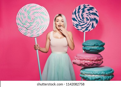 Pretty young girl with blonde hair wearing top and skirt standing with huge sweet lollypop and macaroons at pink background, candy lover, Alice in Wonderland concept.