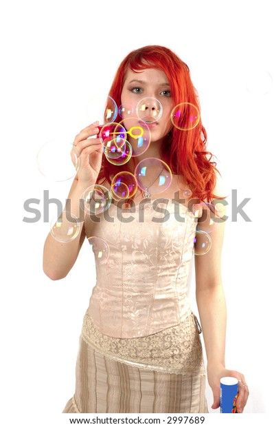 Pretty young girl blowing soap bubbles isolated on white