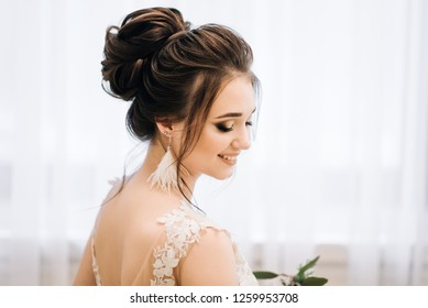 Pretty young girl.  Boudoir morning of the bride. Bride with luxurious hair and makeup. Accessories with feathers