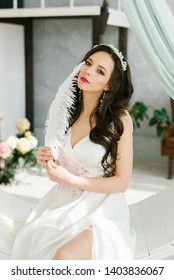 Pretty young girl. Boudoir morning of the bride. Bride with luxurious hair and makeup. Handmade hair decoration. Holds a white ostrich feather