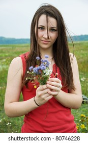 pretty young girl with a bouquet of wildflowers  in summer meadow