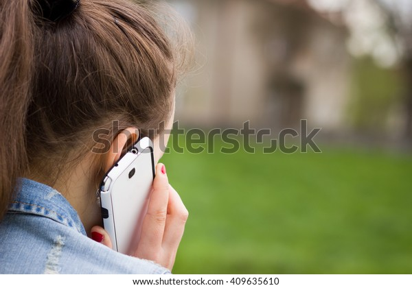 Pretty young girl calling to her work / job and solving problem; looking sad and concentrated (focus on ear; shallow DOF)