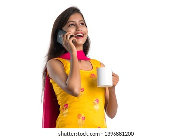 Pretty young girl calling on smartphone device while drinking tasty coffee or tea beverage