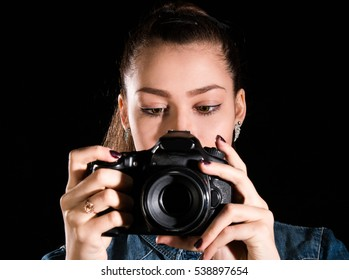 Pretty young girl with a camera over black background