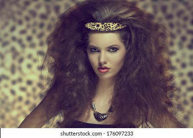 pretty young girl with creative curly hair-style posing with sexy make-up and leopard accessory in the hair and necklace