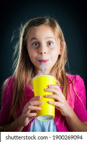 Pretty young girl drinking a slush.
