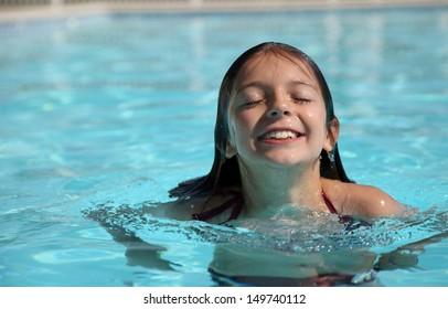 Pretty young girl emerging from swimming pool