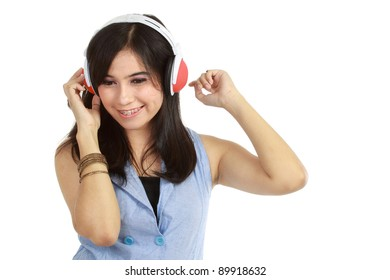 Pretty young girl enjoys listening music. Isolated white background