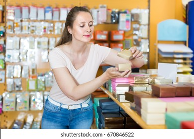 Pretty young girl with gift boxes in her hands in store