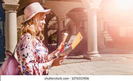 Pretty young girl in the hat and backpack reading a tourist leaflet and smiling